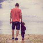 Vater mit Kind an der Hand am Wasser