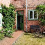 Backsteinhaus mit Sitzecke und offener Tür